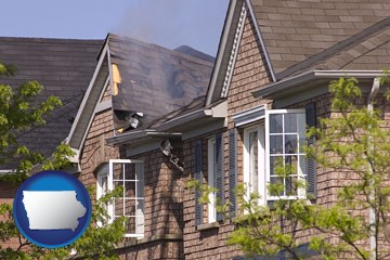house fire damage with a smoldering roof - with Iowa icon