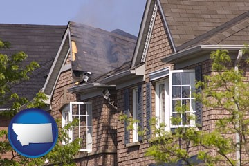 house fire damage with a smoldering roof - with Montana icon