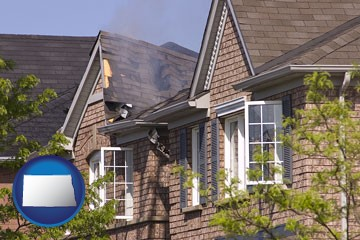 house fire damage with a smoldering roof - with North Dakota icon
