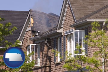 house fire damage with a smoldering roof - with Nebraska icon