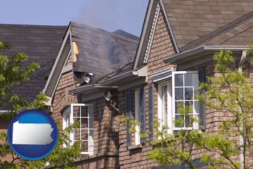 house fire damage with a smoldering roof - with Pennsylvania icon