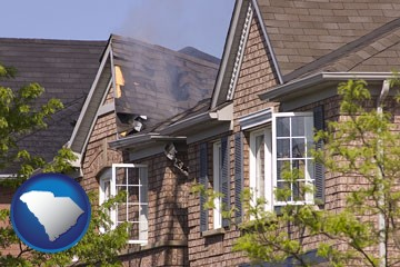 house fire damage with a smoldering roof - with South Carolina icon