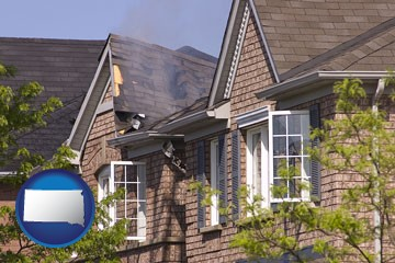 house fire damage with a smoldering roof - with South Dakota icon