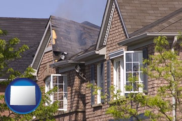 house fire damage with a smoldering roof - with Wyoming icon