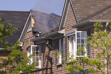 house fire damage with a smoldering roof